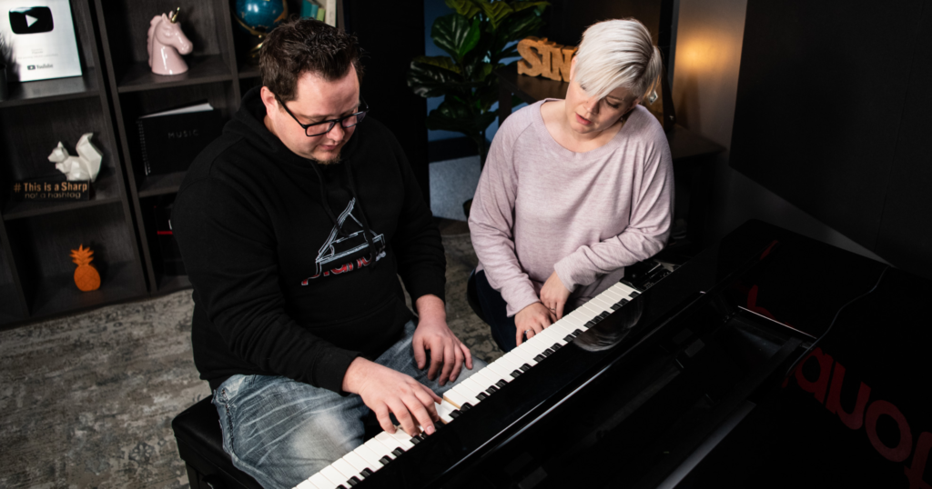 Lisa sits next to man with brown hair and glasses playing piano.
