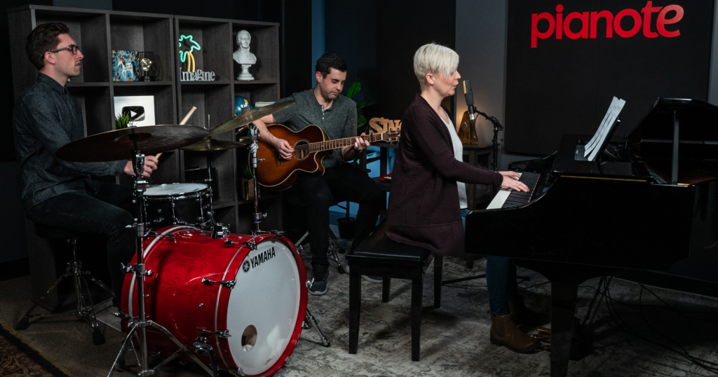 Becoming a multi-instrumentalist can help you join a band. Band in Pianote studio including drummer, acoustic guitarist, and Lisa playing piano and singing.