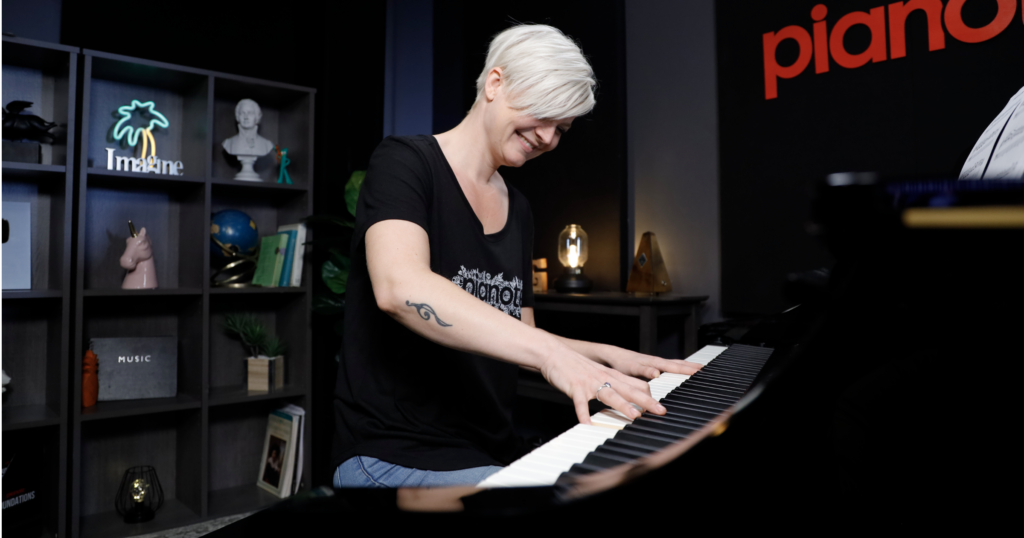 Lisa smiling playing piano in black Pianote t-shirt, shot from a lower angle.