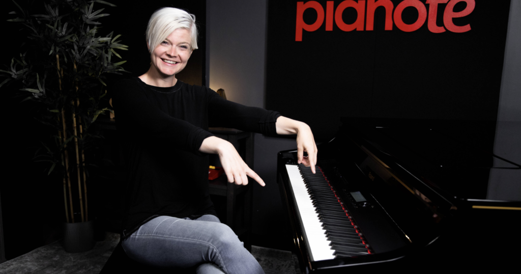 Lisa in black long sleeve shirt pointing at piano with two hands.