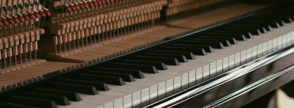 Upright piano keyboard with hammers exposed.