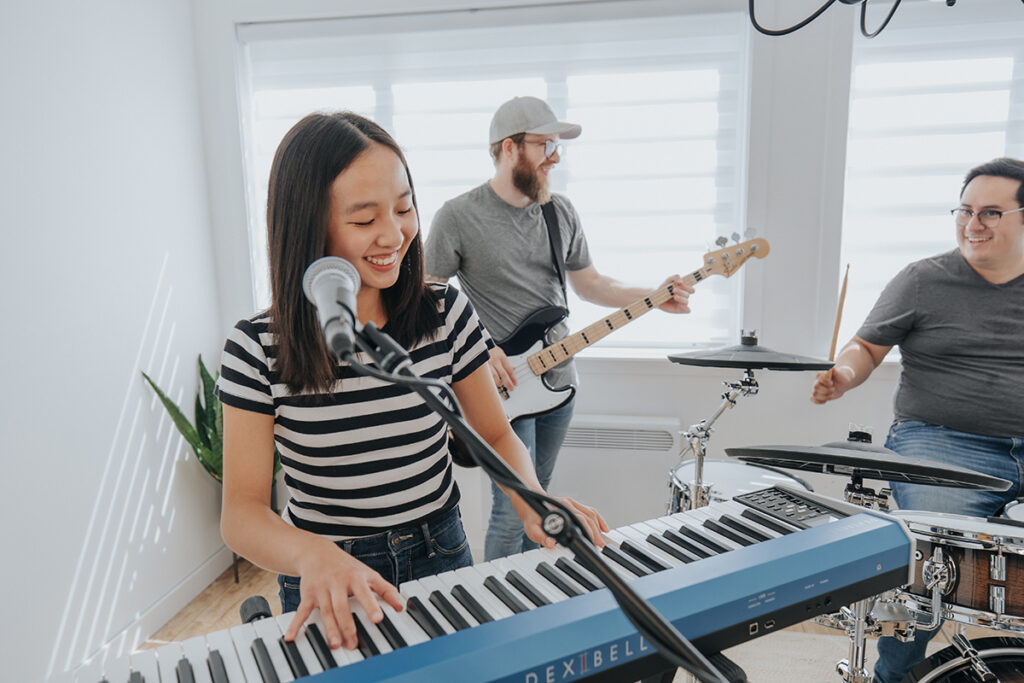 Girl in stripy shirt playing light blue keyboard with mic in front of band with drums and bass.