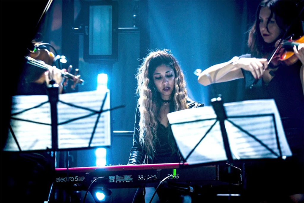 Woman with long curly hair sitting at red keyboard on stage next to violinists in blue neon lighting.