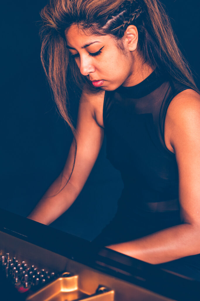 Summer Swee-Singh - young woman with amber-highlighted hair in black dress behind grand piano, playing, with inside of piano slightly exposed.