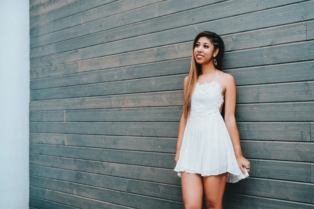 Summer Swee-Singh - young woman with long amber highlighted hair in short white dress smiling and standing against wooden plank wall.
